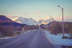 有一辆汽车的冻街道在路在Skjelfjord,当一座巨大的山用雪盖在Lofoten海岛 免版税库存图片