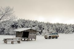 有一辆汽车的木房子在一个多雪的森林里 免版税图库摄影