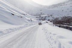 有一辆汽车的路在山的冬天 库存照片