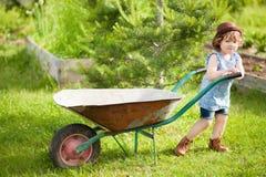 有一辆独轮车的白肤金发的小女孩在国内庭院里 免版税库存图片