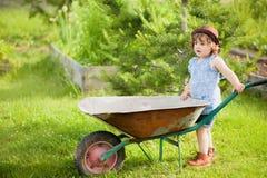 有一辆独轮车的白肤金发的小女孩在国内庭院里 库存照片