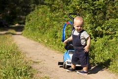 有一辆玩具汽车的滑稽的小孩在步行在公园 免版税库存图片