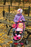 有一辆玩具婴儿推车的女孩在秋天 免版税库存图片