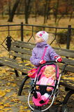 有一辆玩具婴儿推车的女孩在秋天 库存图片