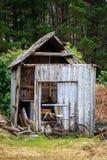 有一辆生锈的自行车的老腐烂的棚子 免版税库存图片