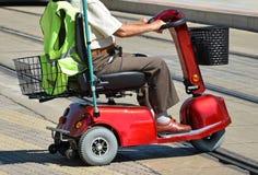 有一辆电动轮椅的老人 库存照片
