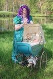 有一辆紫色假发和古董摇篮车的加工好的妇女用gla填装了 免版税库存照片