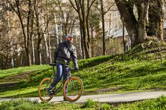 有一辆自行车的一个人在公园 春天在城市 免版税库存图片