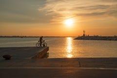 有一辆自行车的一个人在日落的码头 库存图片