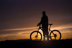 有一辆自行车的一个人在日落背景 免版税库存照片