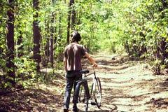 有一辆自行车的一个人在森林夏天森林、绿色叶子、绿色树和草里 守旧派自行车 免版税库存图片
