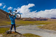 有一辆自行车的一个人在高山背景  Suek通行证 吉尔吉斯斯坦 免版税库存照片