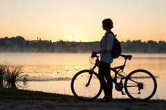 有一辆自行车的一个女孩在湖附近夏天早晨 库存图片