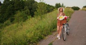 有一辆自行车的一美女在帽子和一件轻的夏天礼服来与在篮子和微笑的花 股票视频