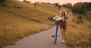 有一辆自行车的一美女在帽子和一件轻的夏天礼服来与在篮子和微笑的花 影视素材