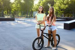 有一辆自行车的可爱的少妇在城市背景在室外的阳光下 活跃人民 有bmx的两个俏丽的女孩 免版税库存照片