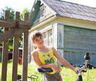 有一辆自行车的女孩反对村庄房子 库存照片