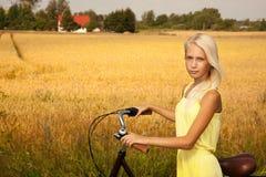 有一辆自行车的女孩在乡下 免版税库存照片