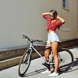 有一辆自行车的女孩在夏天 库存图片