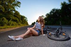 有一辆自行车的女孩在日落 库存照片