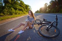 有一辆自行车的女孩在日落 免版税图库摄影