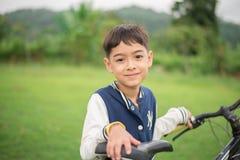 有一辆自行车的小男孩在公园 免版税库存照片