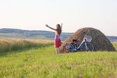 有一辆自行车的少妇在与干草堆的领域晴朗的da的 库存照片