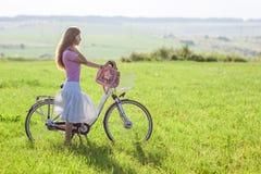 有一辆自行车的少妇在绿色领域在一个晴天 免版税库存照片