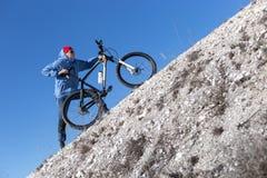 有一辆自行车的年轻人在一座多白粉山 库存图片