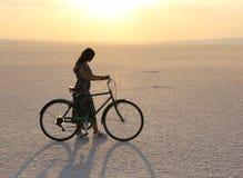 有一辆自行车的未认出的女孩在日落期间的盐湖 免版税图库摄影