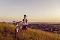 有一辆自行车的男孩在小山 免版税库存照片