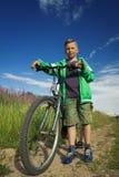 有一辆自行车的年轻男孩本质上休息 免版税库存照片