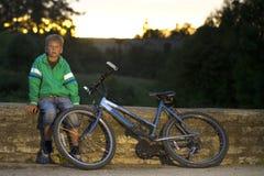 有一辆自行车的年轻男孩本质上休息 库存图片