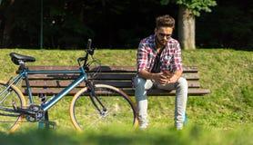 有一辆蓝色自行车的英俊的人 免版税图库摄影