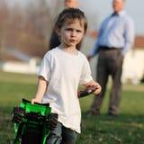 有一辆被剥皮的下巴运载的玩具卡车的小孩男孩 库存图片