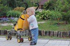 有一辆婴儿推车的一个小男孩在庭院里 免版税图库摄影