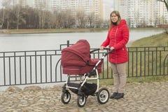 有一辆婴儿推车的女孩在步行 免版税库存图片