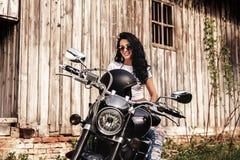 有一辆经典摩托车的c美丽的深色的妇女 免版税库存图片