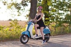 有一辆滑行车的一个女孩在乡下公路 图库摄影