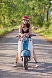 有一辆滑行车的一个女孩在乡下公路 库存照片
