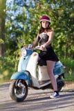 有一辆滑行车的一个女孩在乡下公路 免版税图库摄影