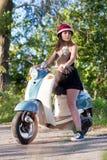 有一辆滑行车的一个女孩在乡下公路 免版税库存图片