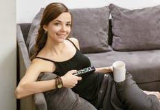 有一遥控的微笑的女孩从电视,说谎在sof 免版税库存图片