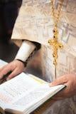 有一部开放圣经的正统教士 免版税库存照片