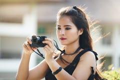 有一部袖珍相机的美丽的妇女摄影师 免版税库存照片