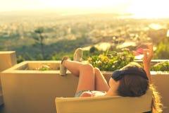 有一长发的女孩在椅子的耳机在阳台听到在日落背景的音乐的 免版税库存图片