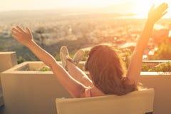 有一长发的女孩在椅子的耳机在阳台听到在日落背景的音乐的 图库摄影