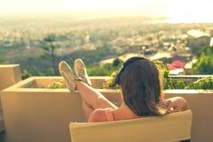 有一长发的女孩在椅子的耳机在阳台听到在日落背景的音乐的 免版税库存照片