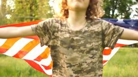 有一面大美国国旗奔跑的一个男孩通过公园 孩子在伪装制服和盖帽打扮 股票视频