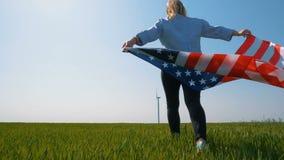 有一面旗子的美国本地人女孩在一个领域的一台巨型风车附近在慢动作 股票视频